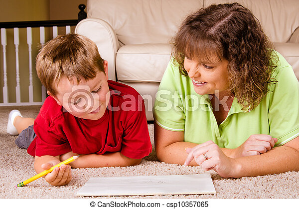 Mother helping child with writing lesson for school while at home - csp10357065