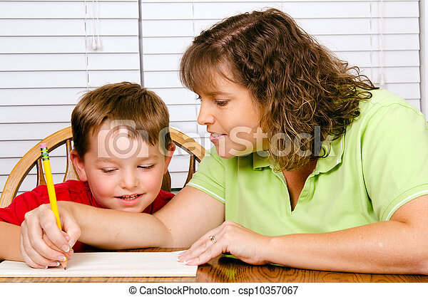 Mother helping child with writing lesson for school while at home - csp10357067