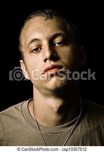 Grungy portrait of young adult man with serious unhappy expression isolated on black - csp10357512