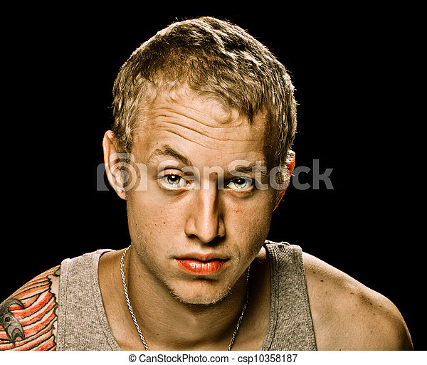 Grungy portrait of young adult man with serious unhappy expression isolated on black  - csp10358187