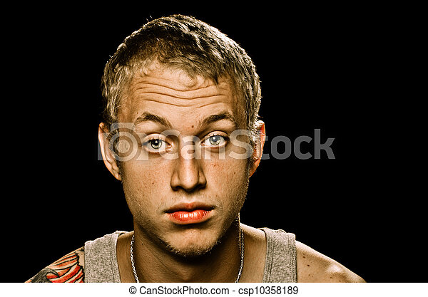 Grungy portrait of young adult man with serious unhappy expression isolated on black  - csp10358189
