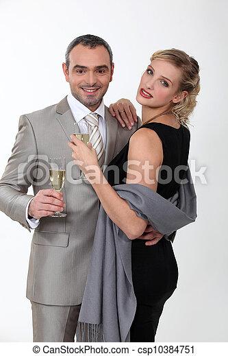 Elegant couple celebrating with champagne on white background - csp10384751