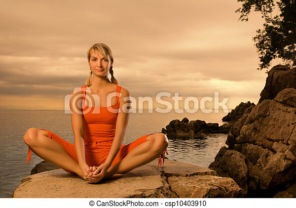 Beautiful young woman doing yoga exercise outdoors - csp10403910