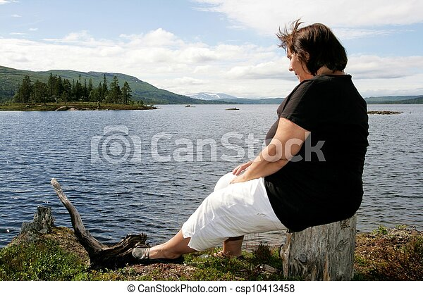 Obese woman sitting by a lake - csp10413458