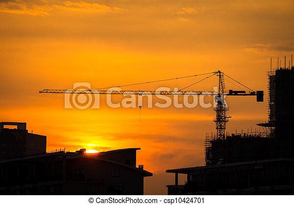Industrial construction cranes and building silhouettes with sunset - csp10424701