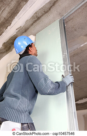 Worker slotting plasterboard into place - csp10457546