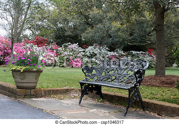 flower garden with wrought iron bench - csp1046317