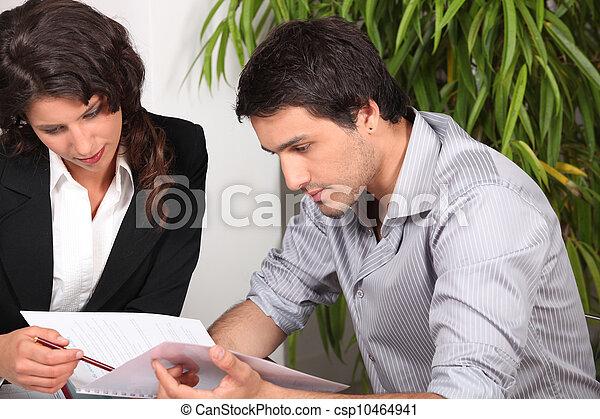 Couple reading through a report - csp10464941