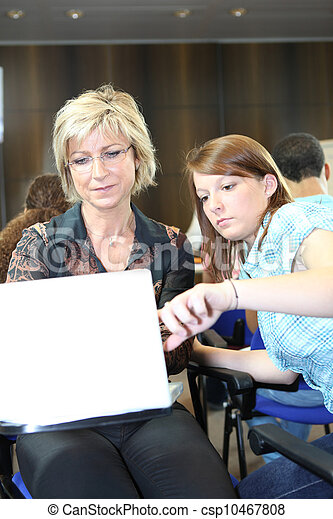 Teacher and student working on laptop - csp10467808