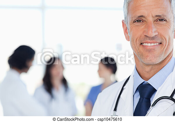 Smiling doctor with his medical interns behind him - csp10475610