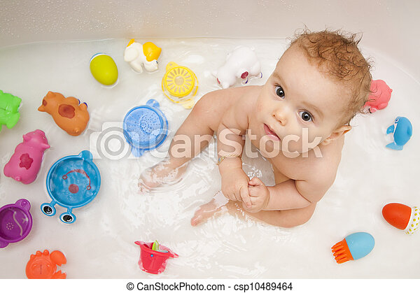 Baby in bath tub with toys - csp10489464