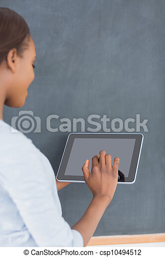 Woman using a tablet computer next to a blackboard - csp10494512