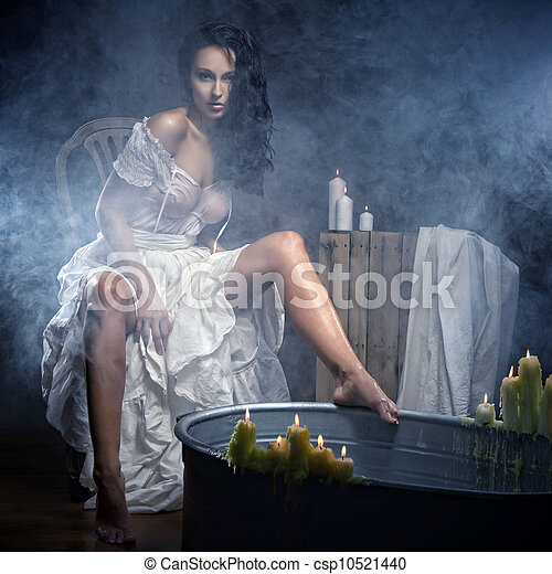 Woman relaxing in bath with candels - csp10521440