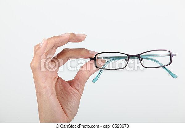 Hand holding pair of eyeglasses