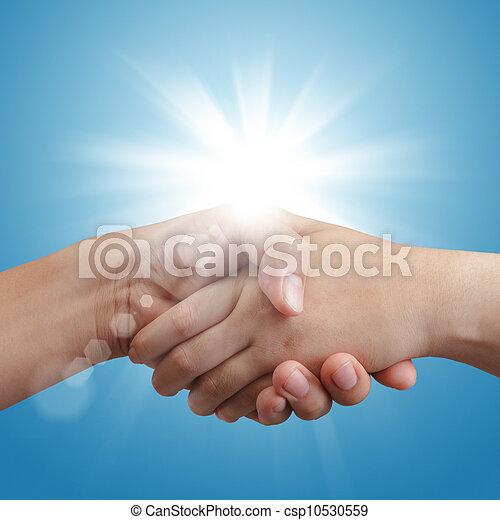 handshake on blue sky and sunlight - csp10530559