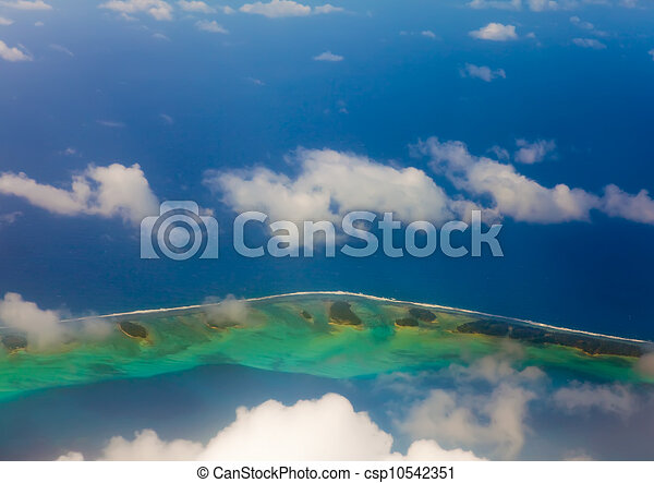 The atoll ring at ocean is visible through clouds. Aerial view. - csp10542351