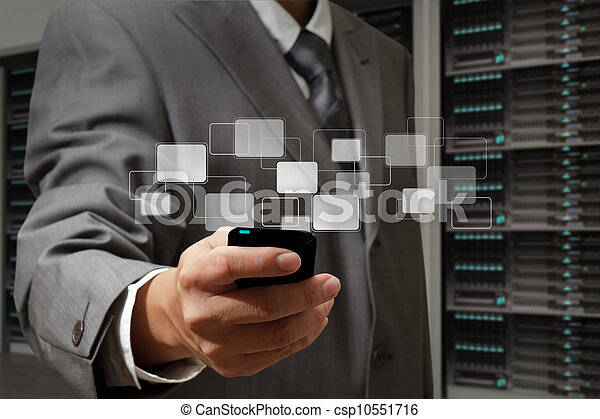 business man holds touch screen mobile phone in server room - csp10551716
