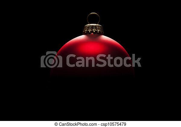 redchristmas ball in tense light on black background