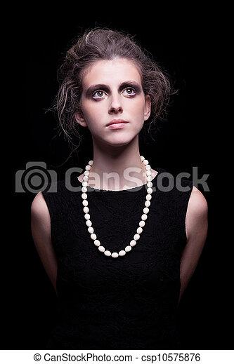 beautiful young woman with elegant black dress, on black background, studio shot - csp10575876
