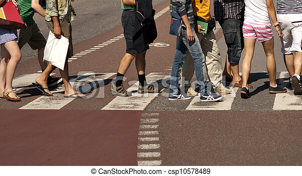 Legs of people crossing a street with bicycle lane