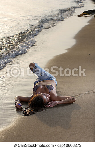 Beautiful young sexy fashion model in jeans by the sea - csp10608273