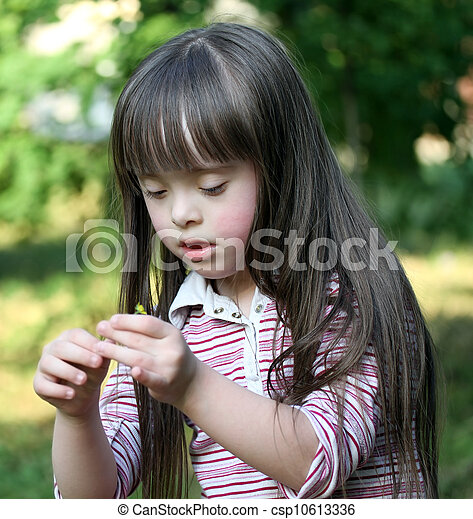 Portrait of beautiful young girl with flower in the park - csp10613336