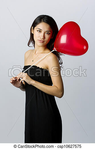 Woman holding a heart shaped balloon for Valentines Day - csp10627575