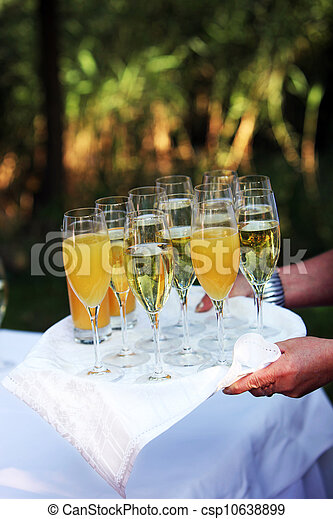 Waiter carrying a tray of champagne flutes anf orange juice for toasting at a formal function or wedding