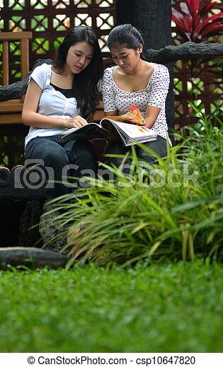 Reading a magazine on park - csp10647820