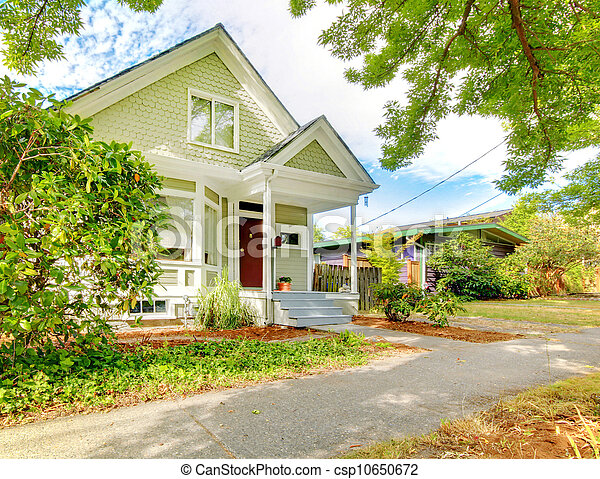 Small cute craftsman American house wth green and white. - csp10650672