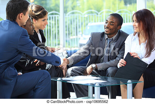Two business man shaking hands with his team in office - csp10695562