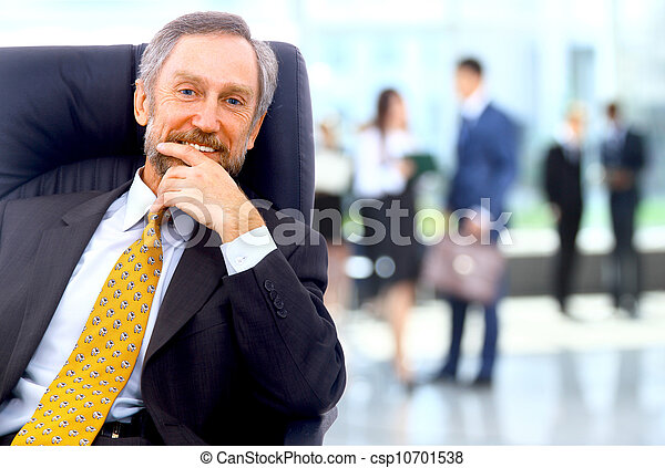 Successful business man standing with his staff in background at office - csp10701538