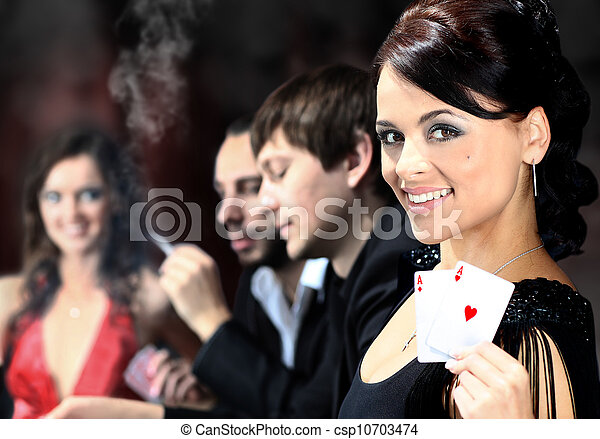 Poker players sitting around a table at a casino - csp10703474