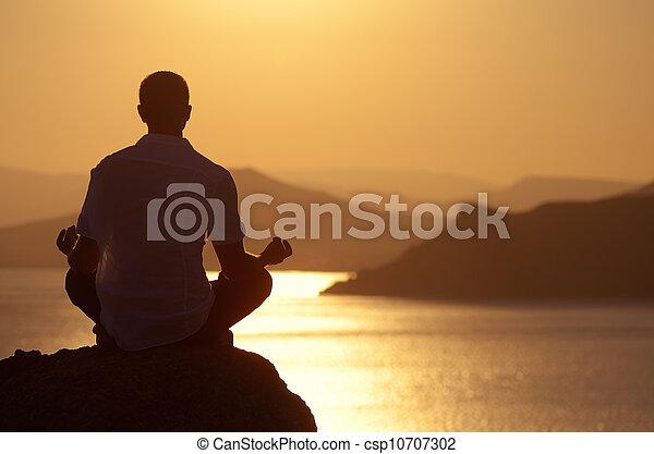 Guy meditating at sunset - csp10707302