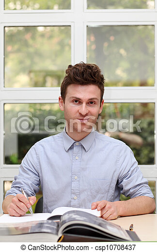 Young adult man writing note - csp10708437