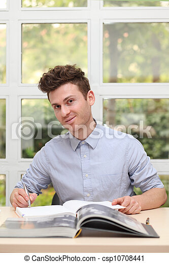Young adult man writing note - csp10708441