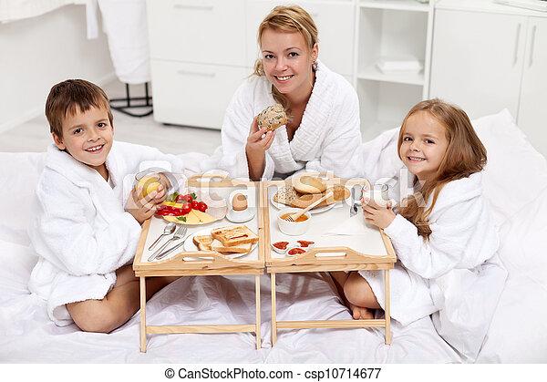 Happy morning - family having a light brekfast in bed