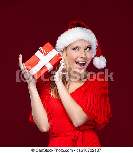 Young woman in Christmas cap hands a gift wrapped with red paper, isolated on purple - csp10722107