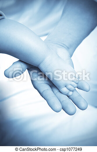 Baby foot and adult hand - csp1077249