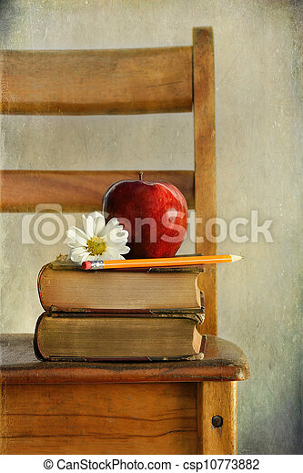 Apple and books on old school chair - csp10773882