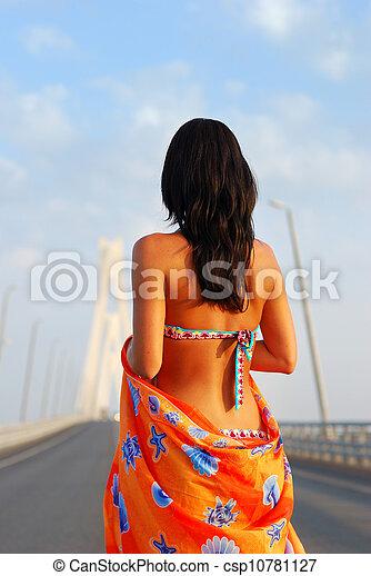 Young adult walking over  bridge - csp10781127