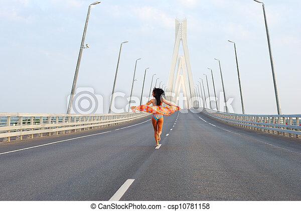 Young adult walking over  bridge - csp10781158