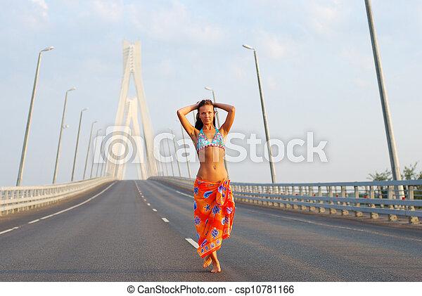 Young adult walking over  bridge - csp10781166