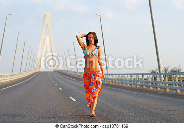 Young adult walking over  bridge - csp10781169