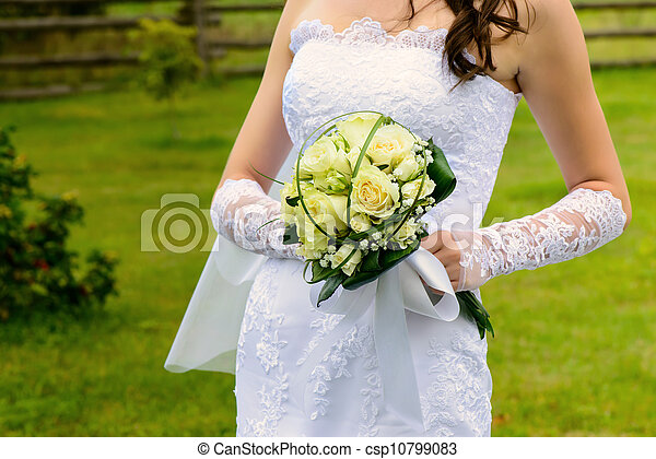 Beautiful wedding bouquet in the hands of the bride - csp10799083