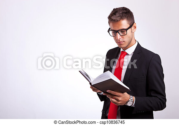 student wearing glasses and reading a law book - csp10836745