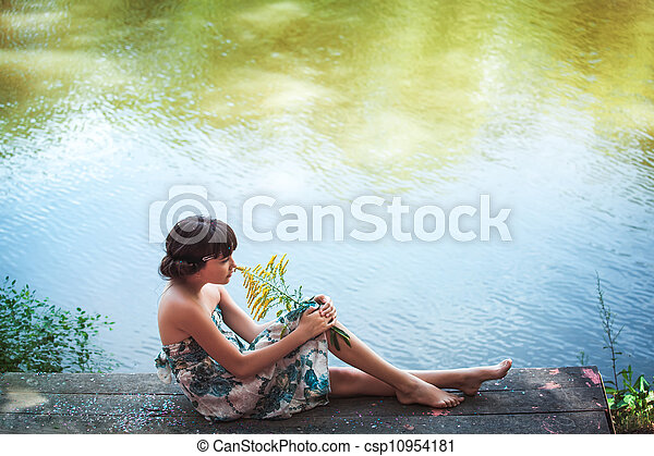 Girl sitting by a lake - csp10954181