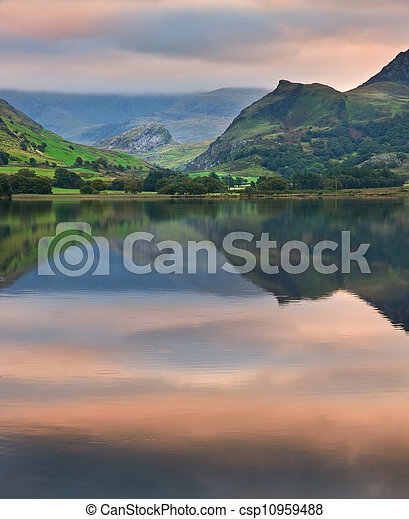 View of Snowdon covered in cloud at sunrise from Llyn Nantlle with reflections in lake and vibrant colors with rowing boats moored at jetty