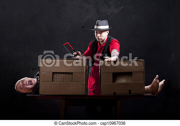 Magician sawing a man in half.