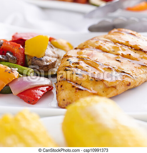 grilled barbecue chicken with vegetables and corn on the cob shot close up - csp10991373